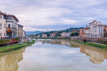 Colorful old buildings on the bank of Arno river in Florence, Italy with reflection in water. Medieval architecture