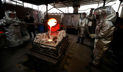 """Workers pour molten bronze into molds of """"The Actor"""" statuettes during a media event on the production of the statuettes for the 25th annual Screen Actors Guild Awards at American Fine Arts Foundry in Burbank"""