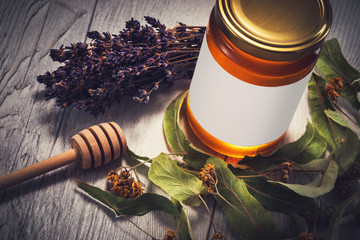 Honey in jar with honey dipper and lavender and linden flowers on vintage wooden background
