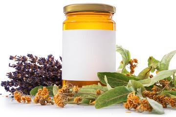 Honey in jar with lavender and linden flowers on vintage wooden background