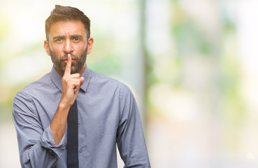 Adult hispanic business man over isolated background asking to be quiet with finger on lips. Silence and secret concept. Wall mural