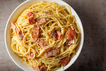Spaghetti carbonara with pancetta, eggs and cheese in white bowl