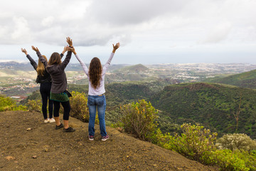Three women with arms up celebrating great views from mountain top on cloudy day in Gran Canaria island. Girl friends hiking in Canary Islands. Outdoors leisure activity, nature connection concepts