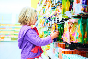 Adorable child blond girl select sweets on shelves in supermarket