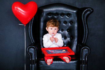 Little boy sitting on the armchair with red framed picture on the St. Valentine's day. Black background and mother's woman day concept