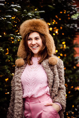 Pretty laughing girl with has a good time in winter weekend. Outdoor portrait of lovable trendy lady with brown hair wears fur hat in december day.