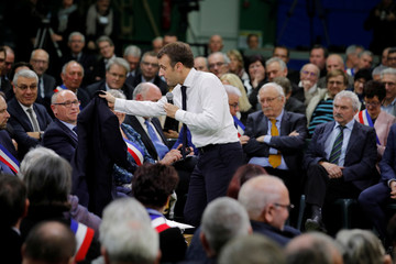 """French President Emmanuel Macron hands over his suit coat during a meeting with mayors from rural Normandy as part of the launching of the """"Great National Debate"""" in Grand Bourgtheroulde"""