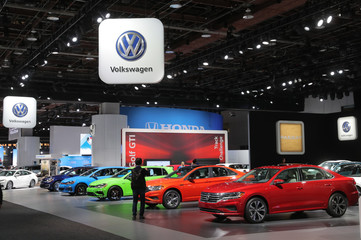 An attendee takes a photograph of Volkswagen cars at the North American International Auto Show in Detroit, Michigan