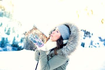 Frau in den Bergen pustet Schnee