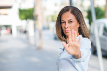 Beautiful middle age hispanic woman at the city street on a sunny day with open hand doing stop sign with serious and confident expression, defense gesture