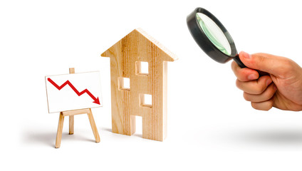 Magnifying glass is looking at the wooden house and red arrow down. concept of falling prices and demand for real estate, the fall in the rate of construction of new housing and buildings. Low quality