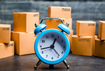 Cardboard boxes and a blue alarm clock. Time of delivery. Limited supply, shortage of goods in stock, hype and consumer fever. Time of delivery. concept of buying and selling goods.