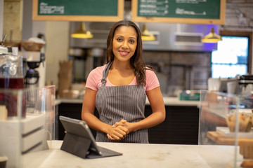 Portrait of female barista standing in cafe
