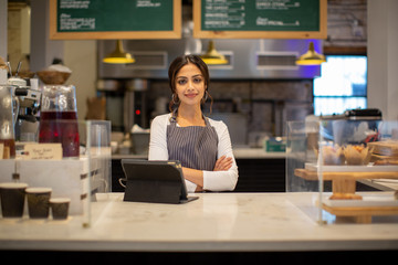 Portrait of smiling female barista standing in cafe
