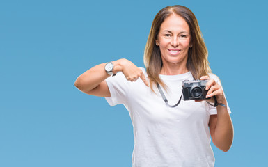 Middle age hispanic woman taking pictures using vintage photo camera over isolated background with surprise face pointing finger to himself