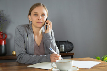 Successful businesswoman negotiating on phone. Young woman in jacket talking on cellphone and writing notes in papers. Confident business woman concept