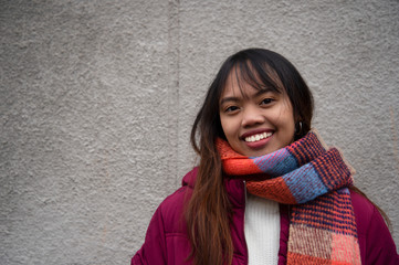 smile Filipino young teen woman Asian portrait with red coat and scarf with grey wall background