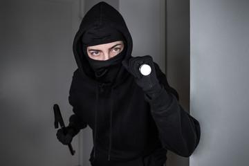 Maskierter Einbrecher dringt mit Taschenlampe und Brecheisen in Wohnung ein