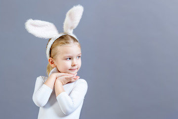 Little girl in white Easter bunny costume on a gray background. Beautiful baby looking towards copy space. Bright festive photo with space for text.