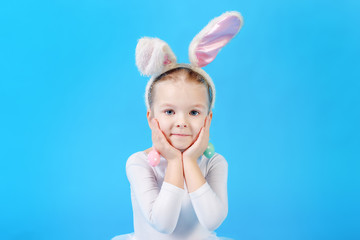 Little girl in a white Easter bunny suit on a bright blue background. Beautiful emotional child.