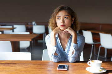 Serious businesswoman with curly hair sitting in coffee shop. Pensive Chinese lady in blouse thinking about plans. Leisure in cafe concept