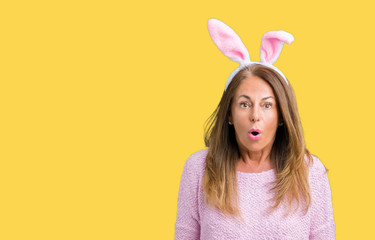 Middle age brunette woman wearing easter rabbit ears over isolated background afraid and shocked with surprise expression