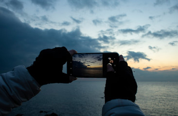 Girl's hand holding smartphone taking sunset photo. Hands in knitted gloves.