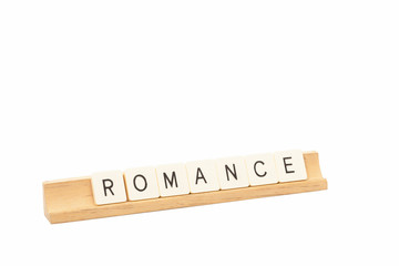 Game tiles on a wooden rack spell out the word Romance