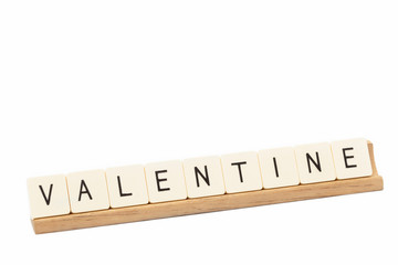 Game tiles on a wooden rack spell out the word  Valentine