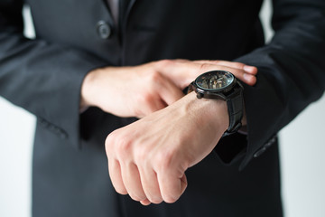 Businessman consulting wristwatch. Cropped portrait of business leader checking time. Time management concept