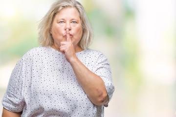 Senior plus size caucasian woman over isolated background asking to be quiet with finger on lips. Silence and secret concept.