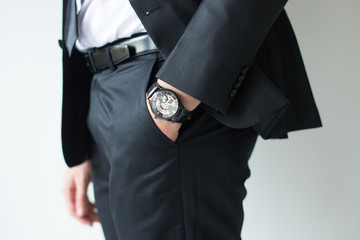 Closeup of watch on businessman wrist. Business leader hand slipping in pocket. Business accessory concept