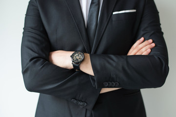 Confident businessman posing with arms crossed. Cropped portrait of business leader in suit with wristwatch. Business success concept