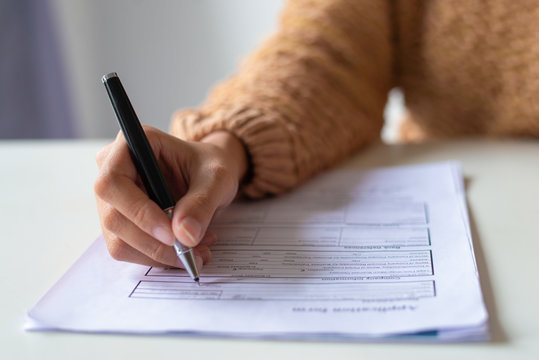 Close-up of lady filling application form. Unrecognizable woman in sweater sitting at table and preparing her resume. Job search concept