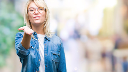 Young beautiful blonde woman wearing glasses over isolated background looking at the camera blowing a kiss with hand on air being lovely and sexy. Love expression.