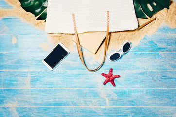 Top view of sandy beach with blue marine planks frame and summer accessories. Background with copy space and visible sand and wood texture. Border composition