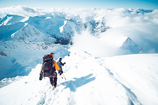 A group of climbers descending a mountain in winter