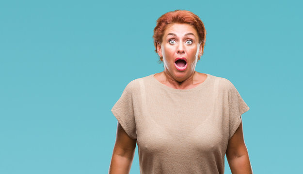 Atrractive senior caucasian redhead woman over isolated background afraid and shocked with surprise expression, fear and excited face.