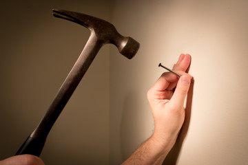 Man's hands prepare to hit a nail with a hammer; on blank wall for picture hanging.