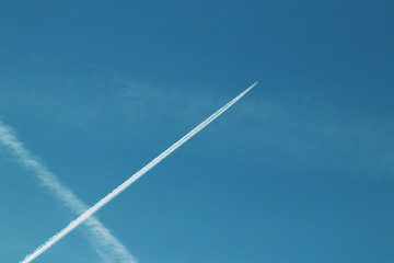 Chemtrails and airplane flying in the blue sky