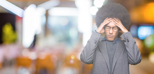 Young african american business man with afro hair wearing glasses suffering from headache desperate and stressed because pain and migraine. Hands on head.