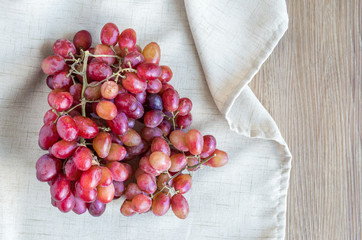 a bunch of red and purple grapes in a tan linen cloth on a wooden table with copy space