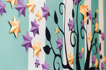 Close-up image of black tree with leaves, yellow and purple six-pointed stars on striped white and turquoise background in apartment. Family tree concept, genealogy, career growth, success metaphor