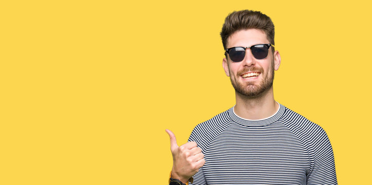 Young handsome man wearing sunglasses doing happy thumbs up gesture with hand. Approving expression looking at the camera with showing success.