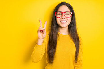 Beautiful brunette woman wearing red glasses over yellow isolated background smiling with happy face winking at the camera doing victory sign. Number two.