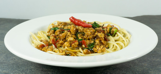 Spaghetti Fried Stir Basil with Minced pork in a dish white on a black stone floor table,food concept..