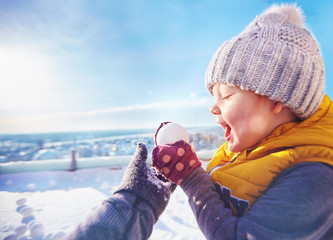 happy toddler baby boy playing snowballs with family at sunny winter day