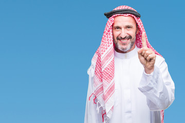 Senior arab man wearing keffiyeh over isolated background showing and pointing up with finger number one while smiling confident and happy.