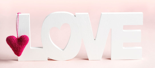 Word Love and pink hearts at pink background