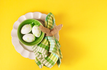 Happy Easter table setting with Easter decoration eggs on yellow background